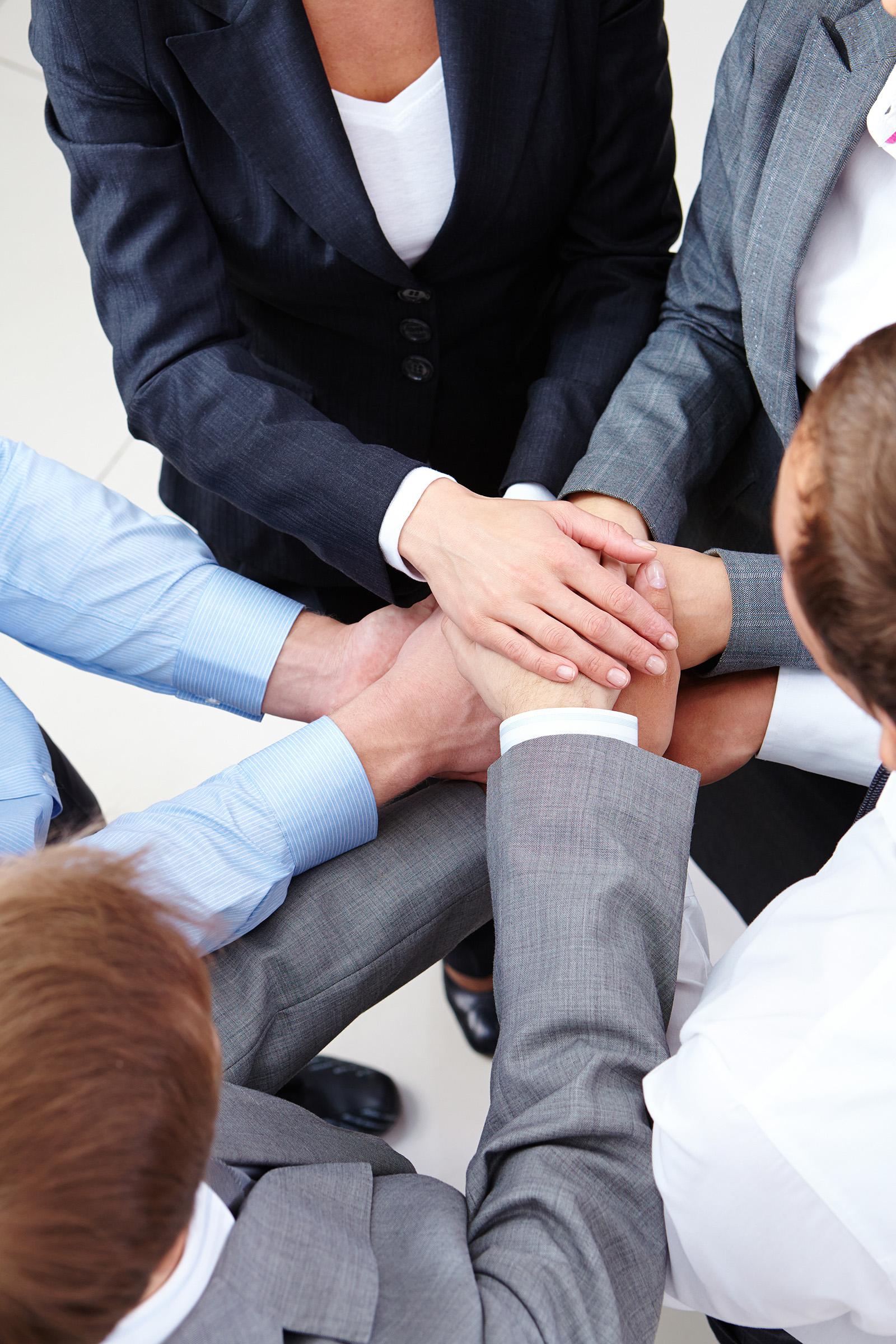 Imagem de cima para baixo de várias pessoas formando um círculo e esticando um dos braços ao centro, sobrepondo-se aos outros braços. Há mulheres e homens.