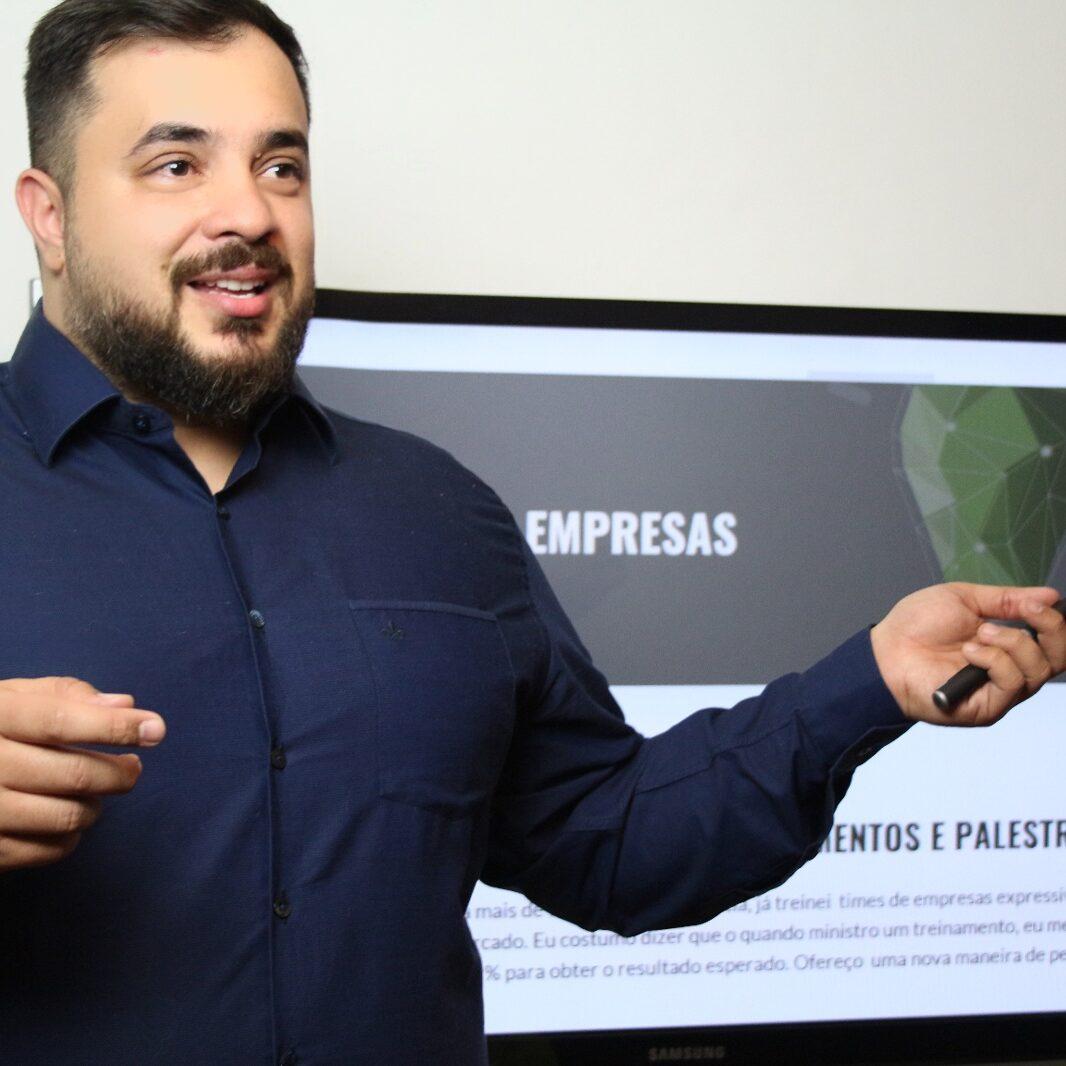 Fredy parece fazer uma apresentação. Ele está na frente de um monitor que exibe seu website. Ele gesticula e veste camisa azul escura.