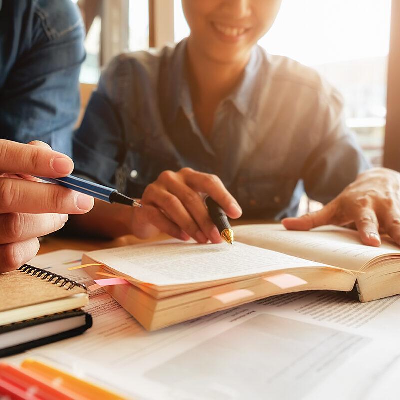 Plano aproximado de uma jovem e um jovem estudando sobre uma mesa com um livro aberto. Ambos seguram uma caneta cada um. Ao fundo, luzes do Sol entram por uma janela iluminando os jovens.